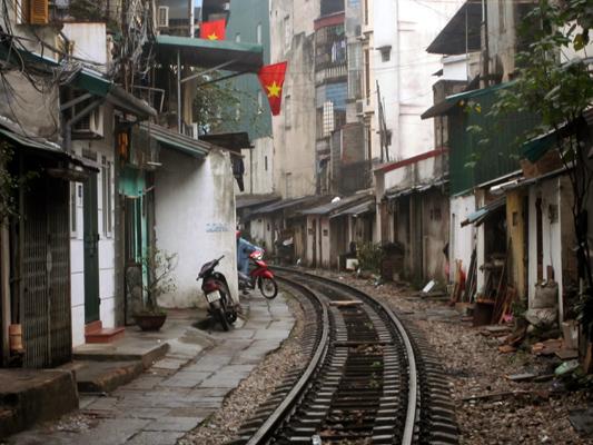 Vía de tren por medio de una calle de Hanoi, Vietnam.